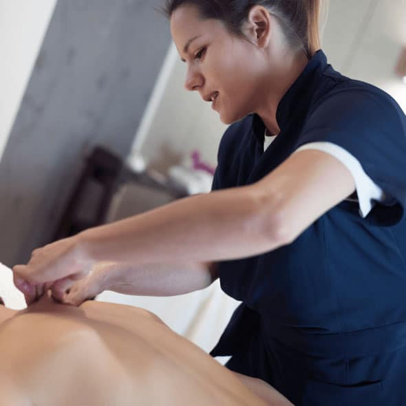 Female massage therapist in blue scrubs gives a client a massage.