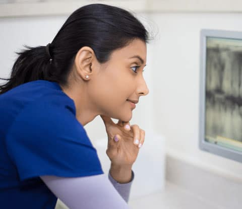 Woman in medical scrubs with a ponytail looks at an x-ray.