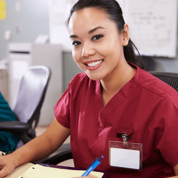 A smiling woman in red scrubs writes something on loose leaf paper.